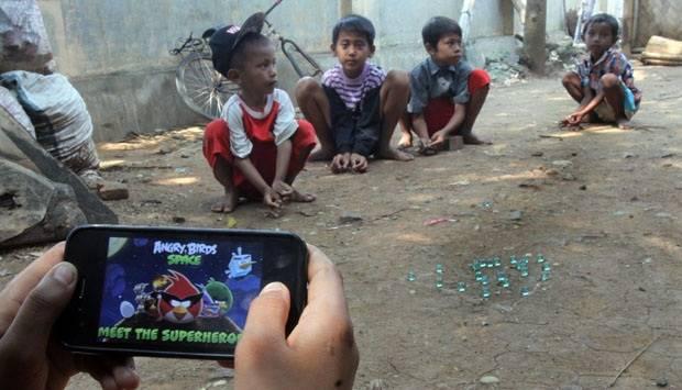 Seorang anak bermain video game ditengah kawannya bermain kelereng di kawasan Cituis, Tangerang, Banten, (10/9). TEMPO/Marifka Wahyu Hidayat