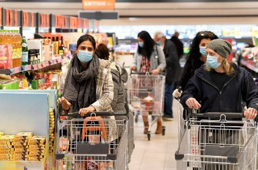 Customers wear face protection in a supermarket in Vienna on April 6, 2020. As of Monday, it is mandatory in Austria to wear such protection in supermarkets with a sales area of 400 m2 or more.