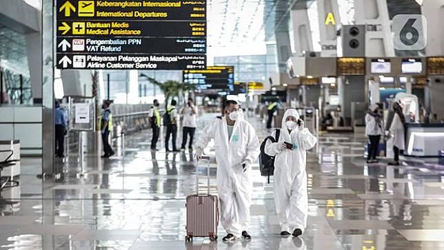 FOTO: Cegah Corona, Calon Penumpang di Bandara Soetta Pakai APD