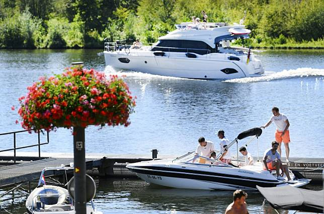 People take a boat in the Meuse river in Arcen, the Netherlands, as a heatwave hits the country on July 31, 2020.