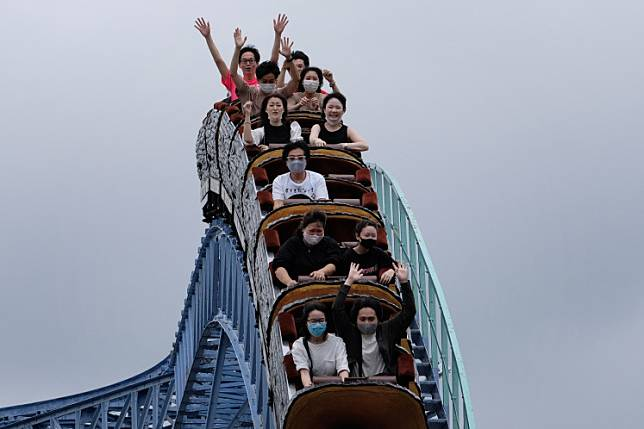 Visitors take a ride on a rollercoaster at the Toshimaen amusement park in Tokyo on July 13, 2020.