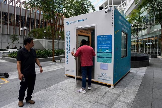 A man (C) enters in a smoking cabin, developed by Southern Globe Corporation (SGC), outside an office building in Singapore on May 22, 2019.
