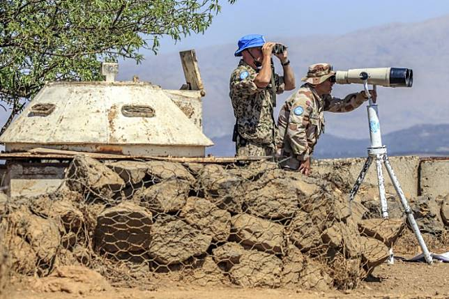 A file photo taken on the Israeli-occupied Golan Heights on September 5, 2014 shows members of the United Nations Disengagement Observer Force Zone (UNDOF) using binoculars to look towards the Syrian side of the Golan Heights.