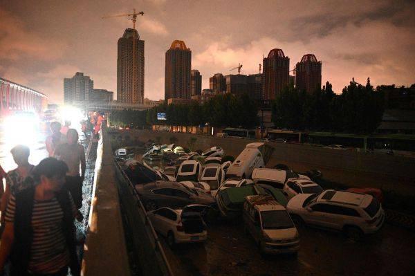 Warga melintas di atas terowongan dimana mobil terseret banjir saat hujan deras di Zhengzhou, Provinsi Henan, China Rabu (21/7)