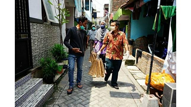 Petugas distribusikan makanan bagi PDP dan ODP yang isolaasi mandiri dalam rumah di Surabaya. (Foto: Antara)