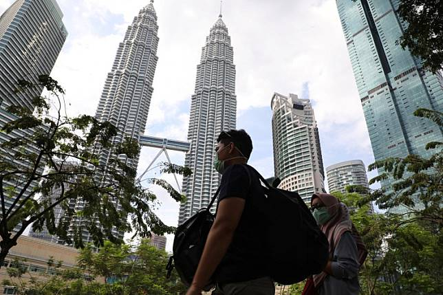 Tourists wearing masks pass by Petronas Twin Towers in Kuala Lumpur, Malaysia, on January 31, 2020.