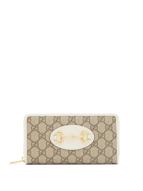 Gucci - Gucci's 1955 Horsebit adorns the front of this beige wallet paying homage to the house's origins in saddlery and luggage. It's crafted in Italy from the iconic GG Supreme canvas trimmed with white leather for a sleek aesthetic and opens to a compartmentalised interior ideal for holding cards, notes and coins. Slip it in a coordinating bag to channel the illustrious heritage.