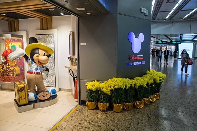 People walk past a Disneyland ticketing office at the high-speed train station connecting Hong Kong to mainland China on January 26, 2020.