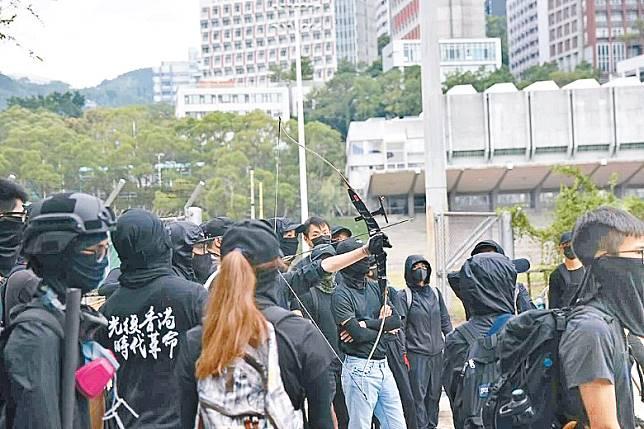 黑衣人取出弓箭,並彎弓狀似射擊。(互聯網)