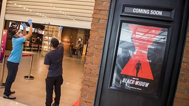 Pekerja menggunakan alat pelindung wajah saat menutup pintu seusai simulasi pembukaan dan peninjauan tempat hiburan bioskop CGV Cinemas di Bandung Electronic Center (BEC), Bandung, Jawa Barat, Kamis (9/7). [ANTARA FOTO/M Agung Rajasa]