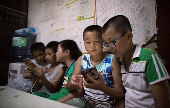 Ilustrasi anak-anak bermain game di ponsel.