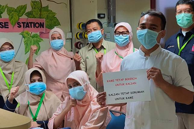 """An image that circulated on social media shows a group of medical workers with a sign that says, """"We stay at work for you. You stay at home for us."""""""