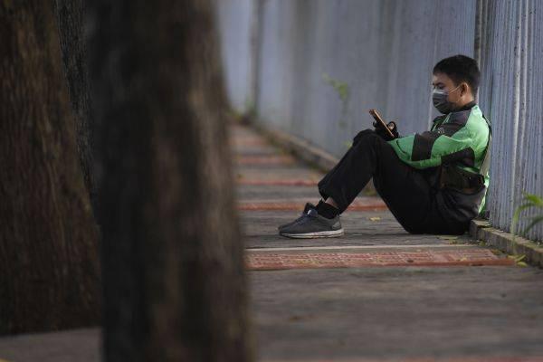 Pengemudi ojek daring menunggu orderan di kawasan Tanah Kusir, Jakarta