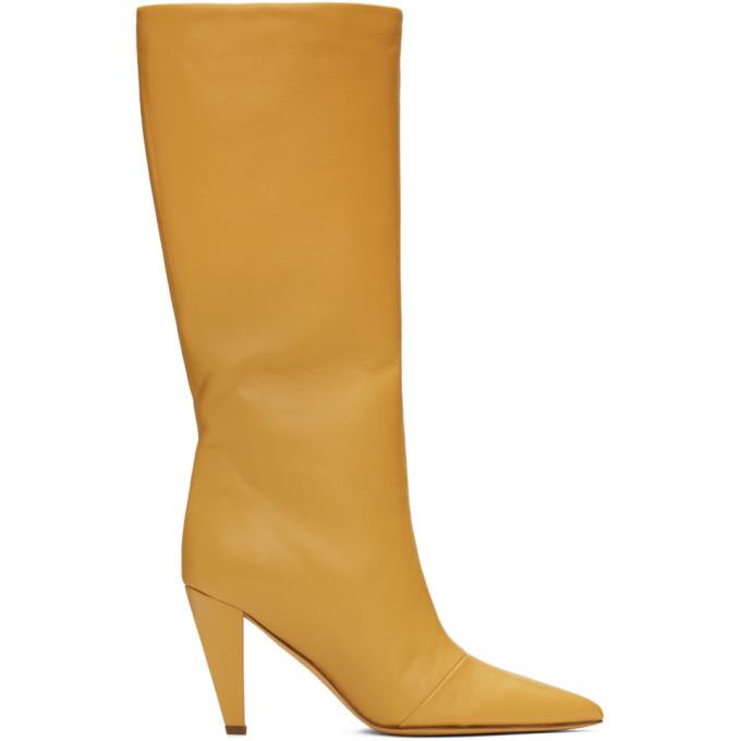 黄色中跟及膝靴,采用抛光皮革面料。尖头,同色皮革内里,同色粗跟和皮革鞋底。跟高约为 7.5cm。供应商配色:Maize