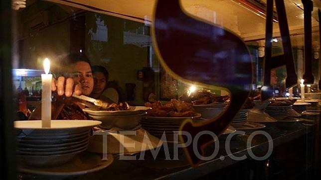 Dengan mengandalkan penerangan lilin, karyawan melayani pembeli akibat pemadaman listrik di sebuah rumah makan di kawasan Sabang, Jakarta, Ahad, 4 Agustus 2019. Dampak padamnya listrik tersebut membuat sejumlah aktivitas warga terhambat. TEMPO/M Taufan Rengganis
