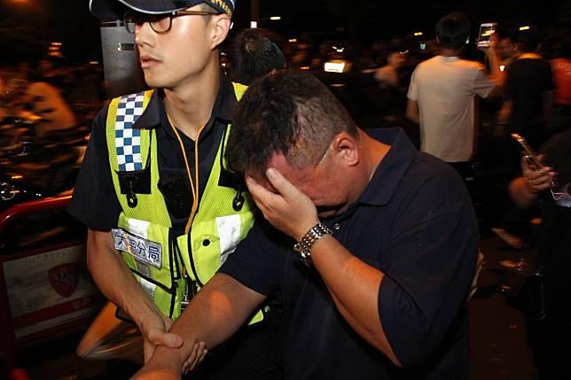 台中市太平警分局偵查隊長陳俊彥(右)在衝突中被辣椒水噴到臉,由警員扶到一旁休息。記者黃寅/攝影