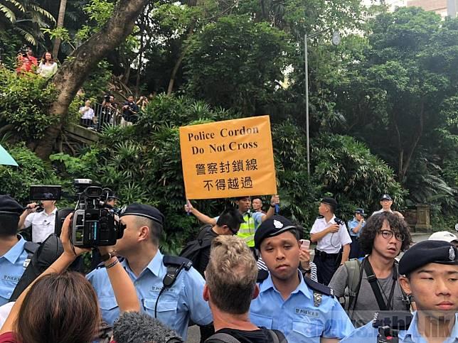 黃之鋒及數名示威者突然衝向警方防線;警員舉起寫有「警察封鎖線,不得越過」的黃旗警告。(實習記者郭衍蔚攝)
