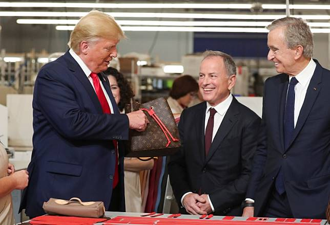 US President Donald Trump holds a purse as Louis Vuitton's CEO Michael Burke and Chairman and CEO of Luxury goods group LVMH Bernard Arnault look on during a visit to the Louis Vuitton Rochambeau Ranch leather workshop in Keene, Texas, US, on October 17, 2019.