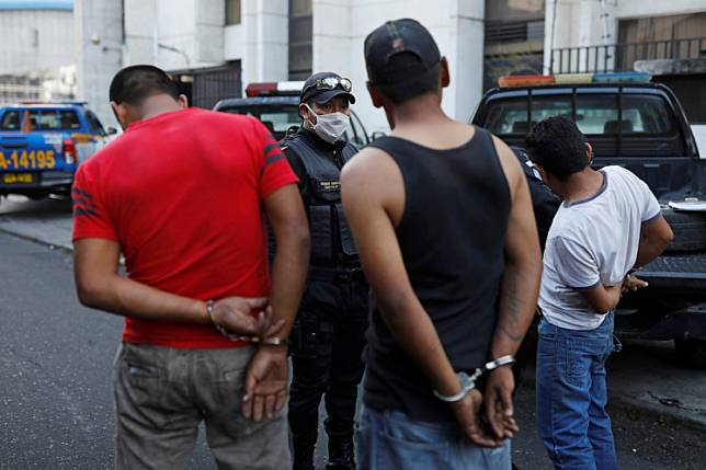 A member of Guatemala's National Civil Police (PNC) talk to men detained for breaking the curfew, imposed as part of the government's measures against the fast-spreading coronavirus disease (COVID-19), in Guatemala City, Guatemala April 3, 2020.