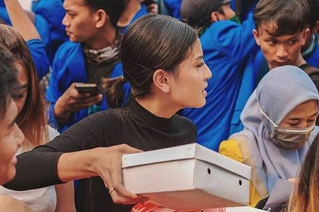 "Instagram celebrity Karin ""Awkarin"" Novilda distributes boxes of food to demonstrators in Jakarta last month."