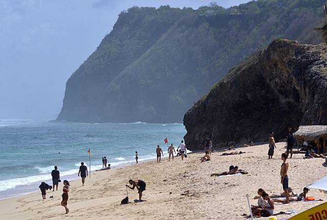 Tourists visit Melasti Beach in Badung regency, Bali, on June 24.
