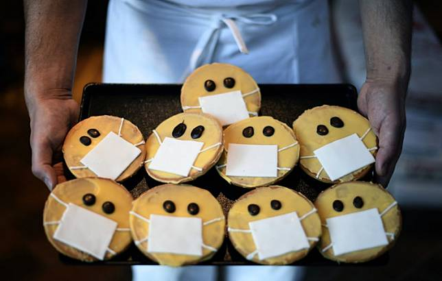 A baker presents biscuits featuring a face with a face mask at the bakery Schuerener Backparadies in Dortmund, western Germany, on March 26, 2020 amidst the spread of the novel coronavirus COVID-19.