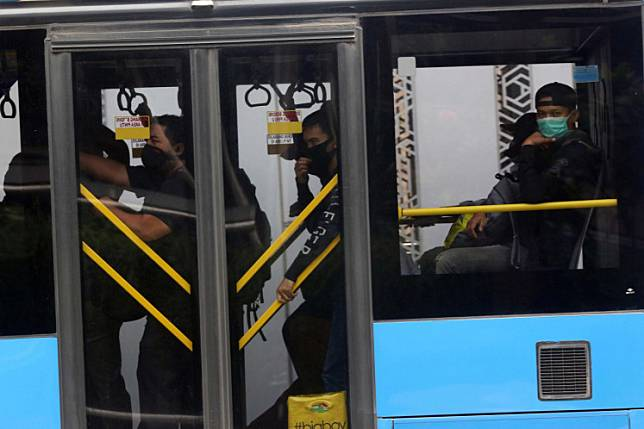 Cover up: Passengers wear face masks onboard a Transjakarta bus as it passes through Jl. MH Thamrin in Central Jakarta on Monday. The obligation for people to wear face masks while in public spaces, including in buses, is stipulated in a newly released gubernatorial instruction that aims to curb the spread of COVID-19.