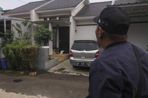Seorang warga melihat rumah terduga teroris yang tampak sepi di kawasan perumahan Bukit Mampang Residence, Depok, Jawa Barat, kemarin.