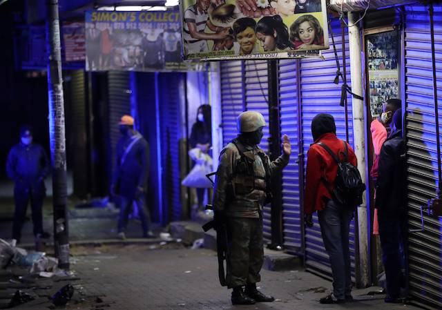 A member of the South African military talks to a man during a patrol as a nighttime curfew is reimposed amid a nationwide COVID-19 lockdown, in Johannesburg, South Africa July 13, 2020.