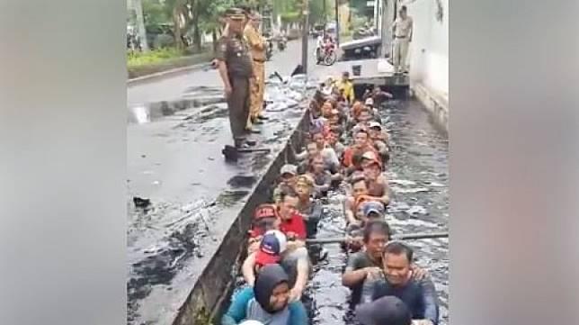 Video pegawai honorer di Jakarta Barat masuk ke got berisi air keruh dan kotor ketika melakukan tes perpanjangan kontrak, viral di media-media sosial. [Facebook]