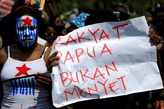 "A protester in an antiracism rally in Central Jakarta holds banner that reads ""Papuans are not monkeys"". The protesters held the rally to urge the government to solve the racial abuse case against Papuan students in Surabaya, East Java."