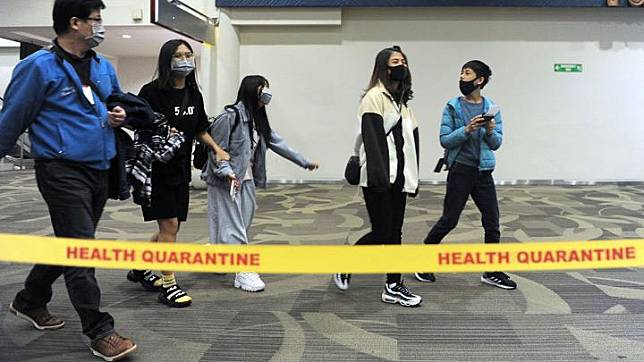 People wearing masks pass by a thermal scanner upon their arrival at I Gusti Ngurah Rai International Airport in Bali, Indonesia January 26, 2020 in this photo taken January 26, 2020.
