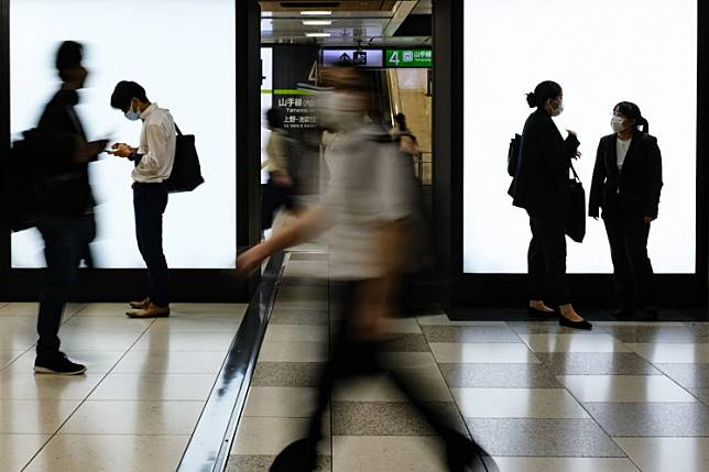 People wearing face masks gather at the Tokyo railway station on July 2, 2020. Health experts put Tokyo on the highest alert for coronavirus infections on Wednesday, alarmed by a recent spike in cases to record levels, while the governor of the Japanese capital said the situation was