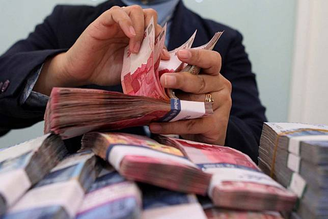 A teller counts rupiah bills at a Bank Mandiri branch in Jakarta in this undated file photo. Indonesia is running out of time to rescue its businesses from the impact of the coronavirus pandemic, and banks should immediately ramp up the  disbursement of promised working capital loans, businesspeople have said.