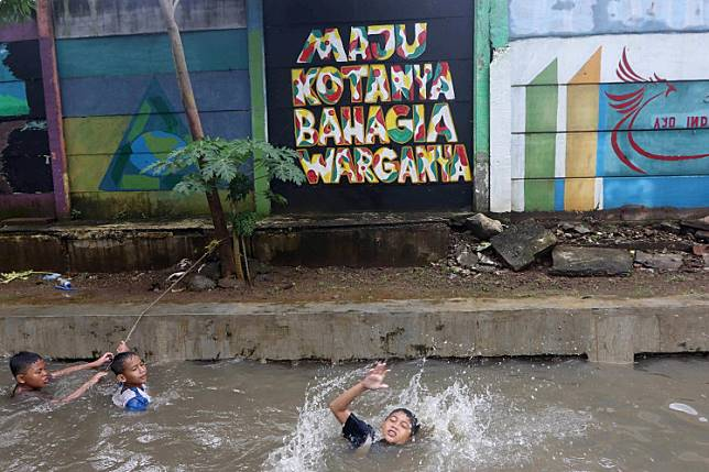 Have fun where you can: Children swim in a flooded area in Bukit Duri, Central Jakarta, on Tuesday. The area was flooded because of the poor condition of the local drainage system.