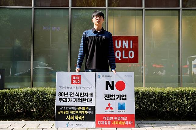 """A university student Bang Seulkichan stands with banners as a protest against recent released Uniqlo commercial in front of a Uniqlo store in Seoul, South Korea, October 22, 2019. The banner reads """"Colonial rule 80 years ago – we remember!"""""""