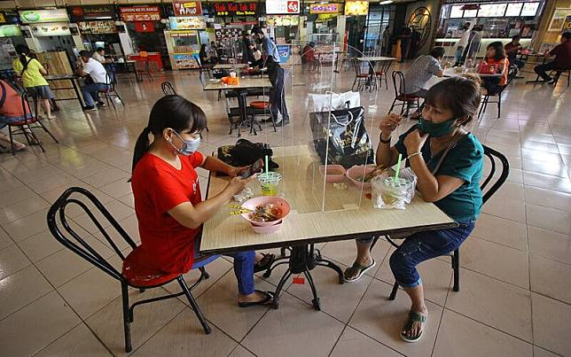 """Pengunjung menikmati makanan di meja makan yang bersekat di pusat jajanan serba ada (pujasera) atau \\""""food court\\"""" Pasar Atom, Surabaya, Jawa Timur, Selasa (9/6/2020)./Antara-Moch Asim\\n"""
