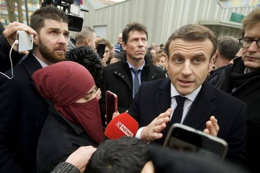 French President Emmanuel Macron, surrounded by people, answers journalists' questions as he arrives to the police station in the district of Bourtzwiller, in Mulhouse, eastern France on February 18, 2020.