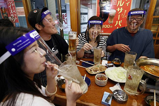 People wearing face shields enjoy drinks and food at a Japanese izakaya pub in Osaka, western Japan, May 25, 2020, after the Japanese government lifted the state of emergency in Tokyo and the remaining 5 areas still under alert for the coronavirus disease (COVID-19), in this photo taken by Kyodo. Picture taken May 25, 2020.