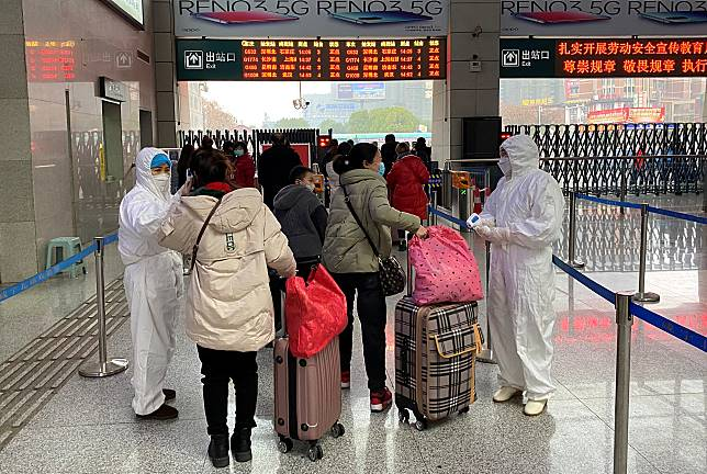 Workers in protective suits check temperatures of passengers arriving at the Xianning North Station on the eve of the Chinese Lunar New Year celebrations, in Xianning, a city bordering Wuhan