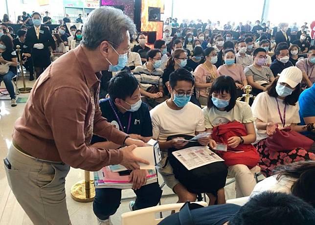 趙國雄(左)早上於銷售處現場向準買家等派發口罩抗疫。