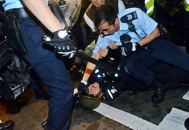 部分示威者被制服在地上。