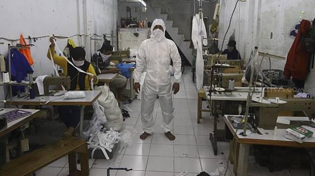 Pekerja kenakan pakaian untuk alat perlindungan diri tenaga medis di Pusat Industri Kecil, Penggilingan, Jakarta Timur, Rabu (24/3).  [Suara.com/Angga Budhiyanto]