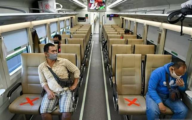 Sejumlah penumpang dengan mengenakan masker di dalam gerbong kereta api luar biasa relasi Gambir-Surabaya Pasar Turi lintas selatan di Stasiun Gambir, Jakarta./Antara