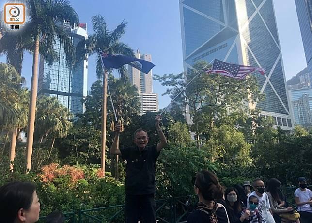 有參加者在遮打花園揮舞美國旗和港英龍獅旗。(袁志豪攝)
