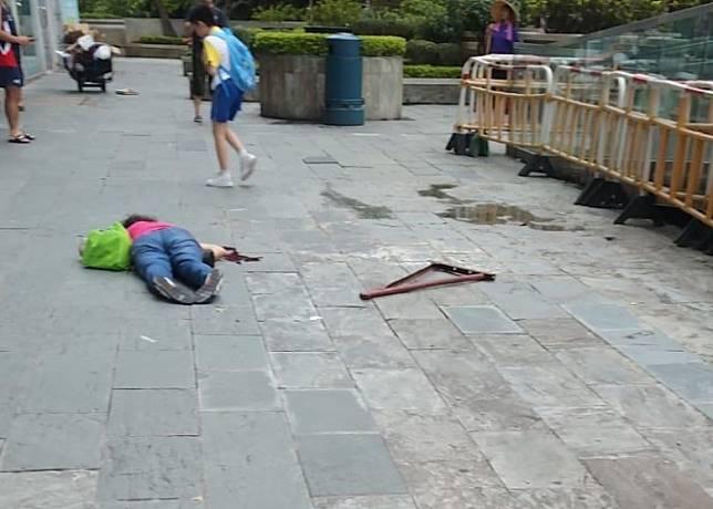 女事主被擊中後倒在地上,狗臂架在身旁,其孫兒站在旁邊。(讀者提供)