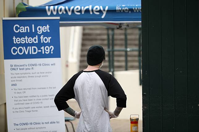 A man waits to be tested for the coronavirus disease (COVID-19) at the front gate of a pop-up clinic at Bondi Beach on April 1, after several outbreaks were recorded in the area in Sydney, Australia.