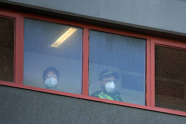Police officers look out the windows of a public housing tower, locked down in response to an outbreak of the COVID-19, in Melbourne, Australia, July 8, 2020. Australian states on Tuesday tightened restrictions on movement as authorities struggle to contain a fresh outbreak of COVID-19 in the country's southeast that has pushed the national tally of cases beyond 10,000.