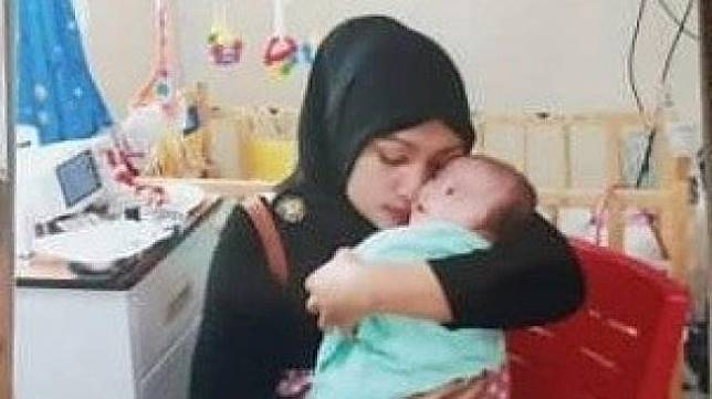 Yulita, warga Aceh memeluk satu dari dua bayi kembarnya. (Istimewa/portalsatu.com)