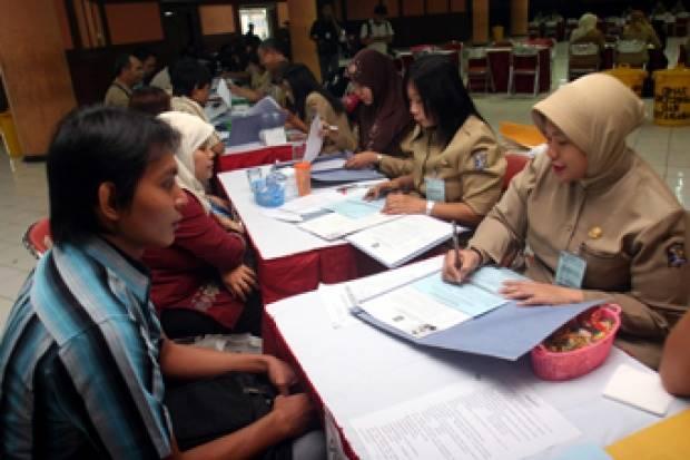 Sejumlah pelamar menyerahkan data diri ke petugas Pendaftaran Calon Pegawai Negeri di Surabaya (26/10). Pemerintah Kota Surabaya membutuhkan 577 PNS, untuk pendidikan, kesehatan, dan tenaga teknis. TEMPO/Fully Syafi